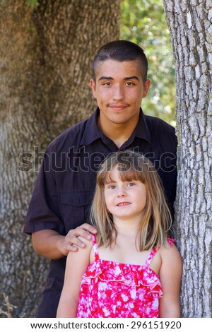 Native American teenager with his caucasian younger sister - stock photo