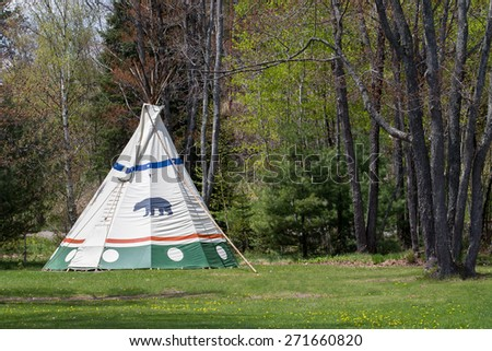 Native American Tepee at Forest Edge - Indian tepee in upper Midwest USA State Park.  Bear clan symbol on tent. - stock photo