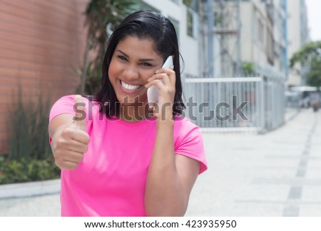 Native american woman at phone showing thumb in city with modern buildings in the background - stock photo