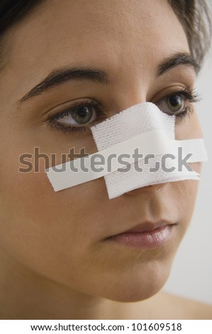 Native American woman with bandage on nose - stock photo