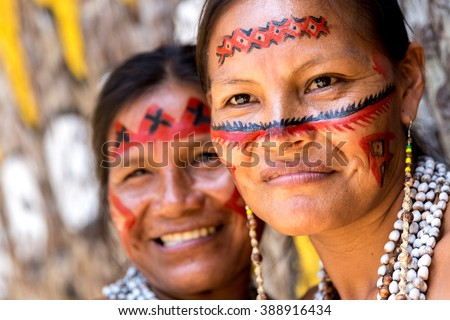 Native Brazilian women smiling at an indigenous tribe in the Amazon  - stock photo