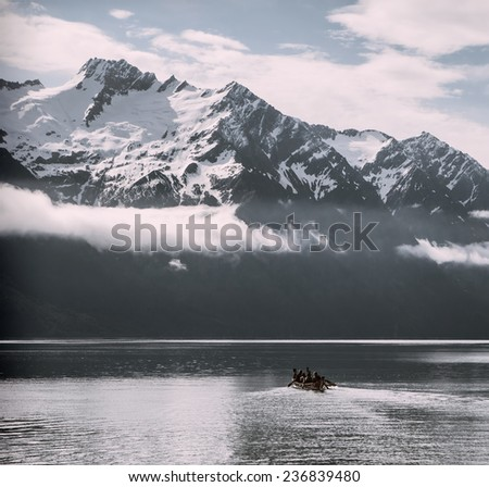 Native canoe heading out to sea in Southeast Alaska with vintage coloration. - stock photo
