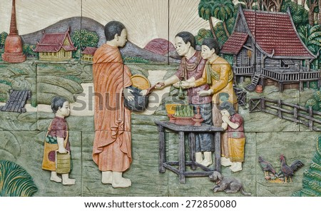 native culture Thai stucco on the temple wall,  Thailand, give food offerings to a Buddhist monk - stock photo