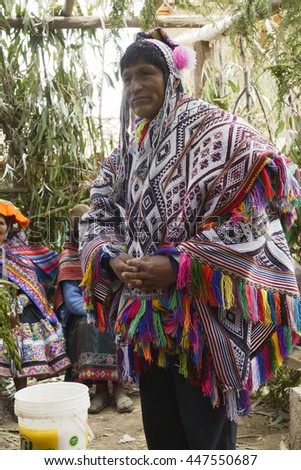 Native Peruvian man wearing a handwoven poncho and chollo, attending his daughter wedding ceremony. Next to him is a bucket with chicha - local beer derived from maize. October 22, 2012, Amaru, Peru