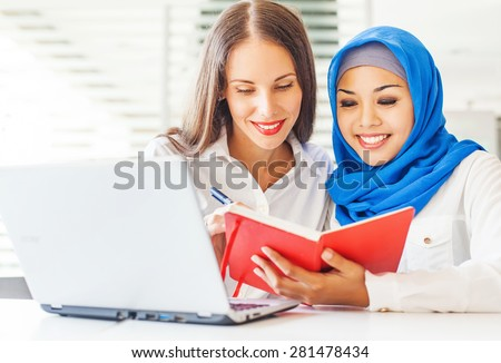 Native speaker teaching a muslim asian girl in a light classroom in college - stock photo