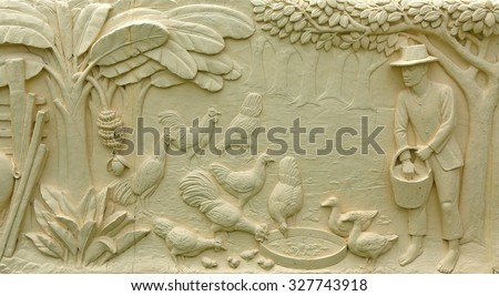 Native Thai culture stone carving on temple wall - stock photo