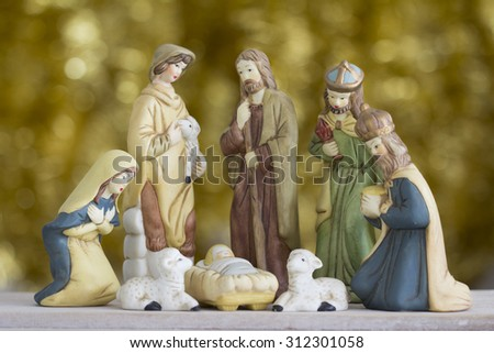 Nativity Scene with Baby Jesus, Mary, Joseph, a Shepherd and a Wise Man on a Golden Background  - stock photo
