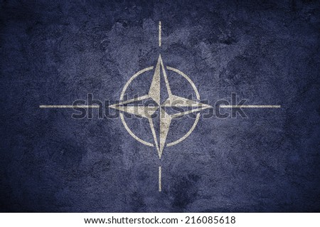 NATO flag on the grunge concrete wall