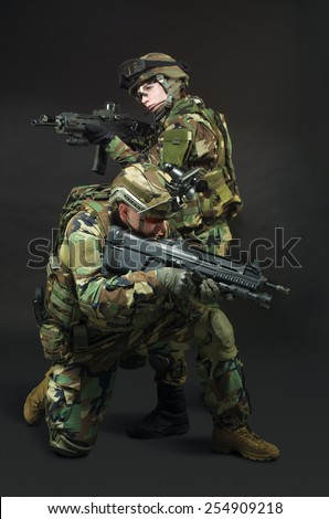NATO soldier in full gear. Military man and woman over black background.