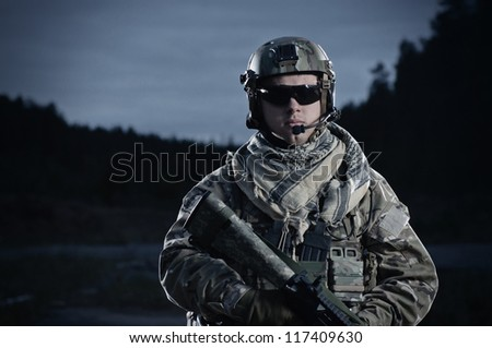 NATO soldier in full gear. Military man on the background of nature.
