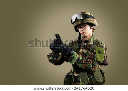 NATO soldier. Military woman over khaki background.