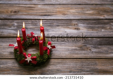 Natural advent wreath with four red candles on wooden old background. - stock photo