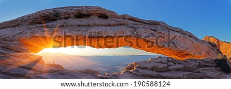 Natural arch glowing in the rays of the rising sun. Mesa Arch, Canyon lands, Utah - stock photo
