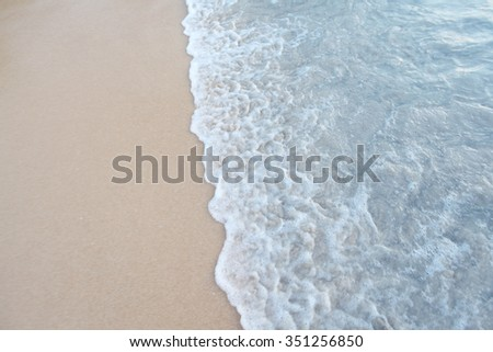 Natural background with wave coming to sandy beach - stock photo