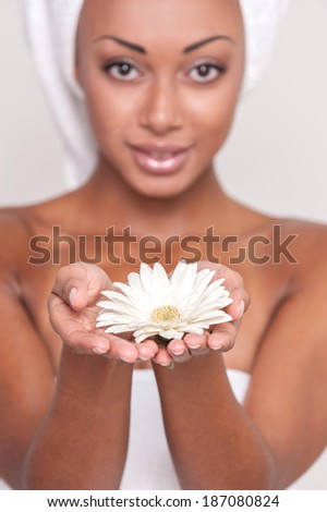 Natural beauty. Beautiful young Afro-American shirtless woman holding flower in her hands and looking at camera while Isolated on gray background - stock photo