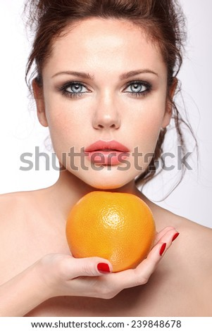 Natural beauty model with nude make up and big lips, grapefruit, red manicure - stock photo