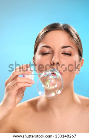 Natural caucasian woman with bubble blower isolated over blue background