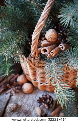 Natural Christmas Decor in a Basket. Nuts, Fir Tree, Cinnamon, Pine cones on Wooden Background. Rustic style - stock photo