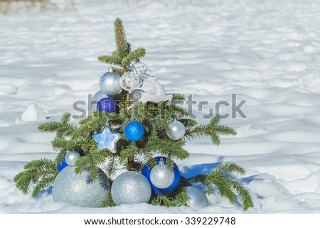 Natural conifer snowy tree decorated with Christmas blue and silver ornaments and baubles - stock photo