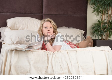 Natural content blonde reading a book while lying on bed - stock photo