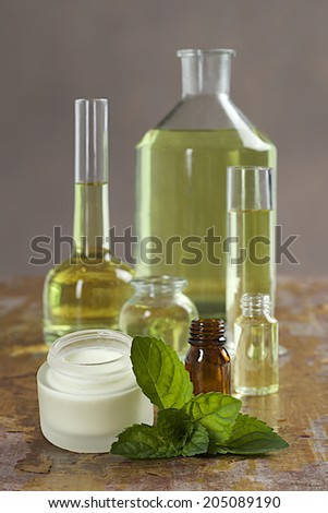 Natural cosmetics - Essence and cream with fresh mint leaves  on wooden table - stock photo