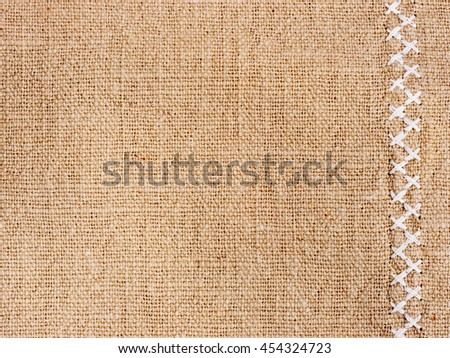 Natural cotton fabric with cross stitch close up as background texture