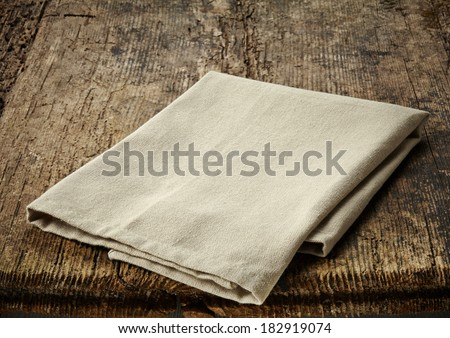 natural cotton napkin on old wooden table - stock photo