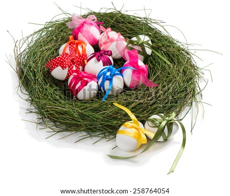 Natural easter eggs with colorful bow in a nest and two nearby  isolated on a white background