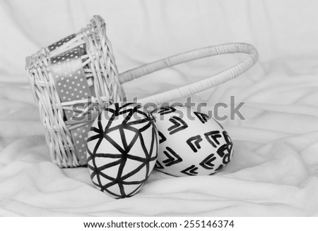 Natural eggs with free hand sketch patterns with basket on cloth background for Easter. Black and white image. - stock photo