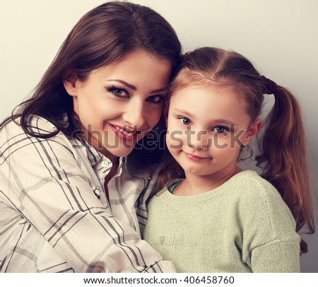 Natural emotional beautiful mother and adorable kid girl hugging in studio. Casual lovely family. Toned closeup portrait - stock photo