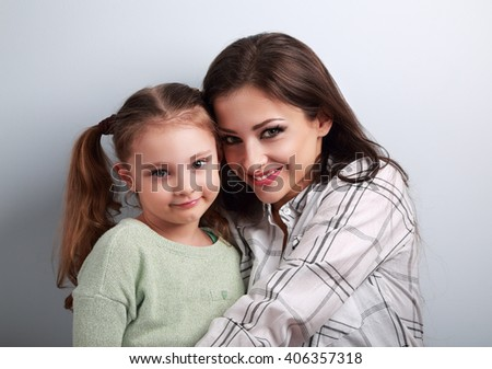 Natural emotional beautiful mother and adorable kid girl hugging in studio on blue background. Casual lovely family - stock photo