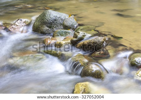 Natural flow of water stream in close up view - stock photo