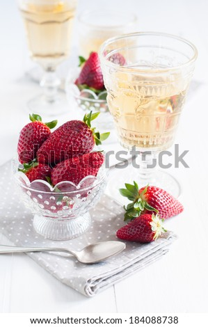 Natural fresh strawberries in a crystal bowl and a few glasses of white wine on a wooden board, drinks and dessert of summer berries. - stock photo