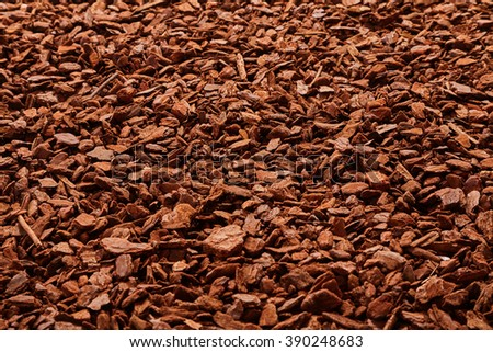 Natural full frame background on angled view of red and brown pieces of tree bark mulch for gardening or natural themes