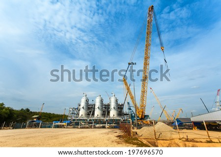 Natural gas and Oil industrial site with a big crane - stock photo