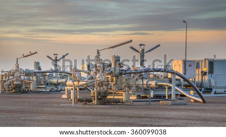 Natural gas production plant in the Waddensea area with pipe line valves - stock photo