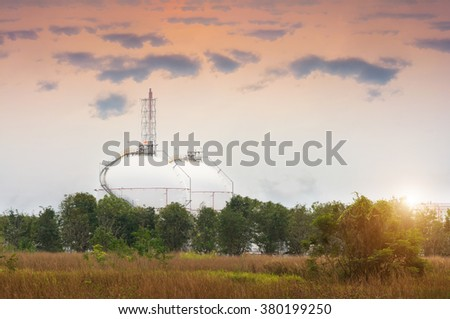 Natural gas tank in the meadow at sunset ,  petroleum , petrochemical plant - stock photo