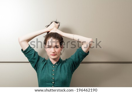 Natural girl grasping her hair and posing wearing a green dress with white dots in front of an iron wall. - stock photo