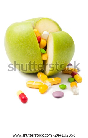 Natural green apple  filled with various colored drugs - stock photo