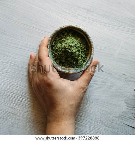 natural hair dye, ceramic bowl with a green pigment, basma green on a white background, green pigment. - stock photo