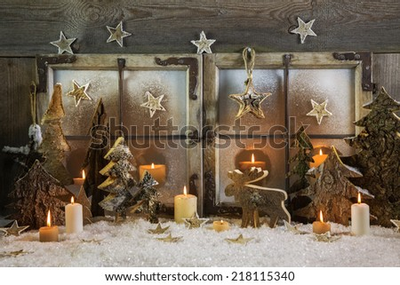 Natural handmade christmas decoration of wood outdoor in the window with candles. Idea for a greeting card. - stock photo