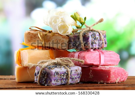 Natural handmade soap, on wooden table, on green background - stock photo