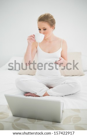 Natural happy blonde drinking from a cup in bright bedroom