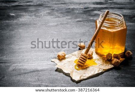 Natural honey with a spoon on old paper. On black rustic table. - stock photo