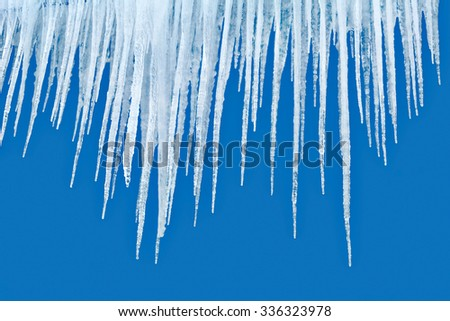 natural icicles isolated on blue background - stock photo
