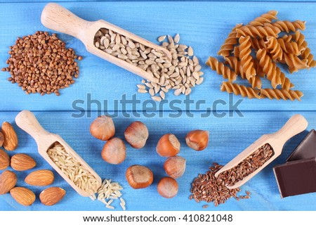 Natural ingredients and products containing magnesium and dietary fiber, healthy food and nutrition, wholemeal pasta, sunflower, buckwheat, almonds, brown rice, hazelnut, linseed, chocolate - stock photo