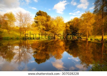 Natural landscape with autumn trees reflected on the surface of a lake. - stock photo