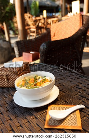 Natural light photo of asian vegetable and mushrooms soup with napkinholder. Shallow DOF view 2 - stock photo