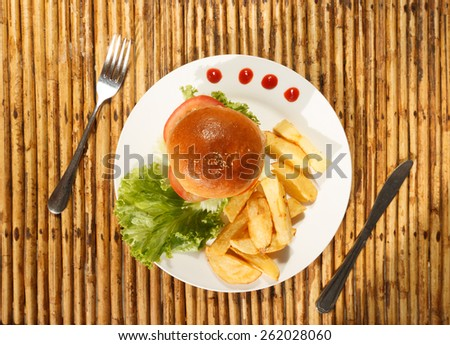 Natural light photo of chicken burger and french fries on plate with tableware top view - stock photo