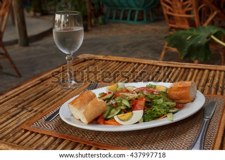 Natural light photo of hard boiled egg with vegetable salad, baguette and glass of water. Seaside, shallow DOF - stock photo